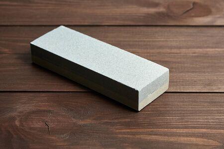 Rectangular double layer sharpening stone. Single grindstone or whetstone sharpener on wooden table background Reklamní fotografie