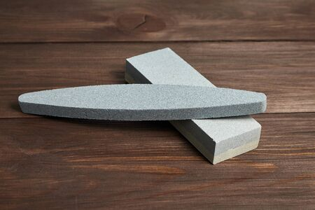 Two grindstones. Oval and rectangular double layer sharpening stone. Whetstone sharpener on wooden table background