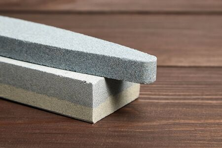 Two grindstones. Oval and rectangular double layer sharpening stone. Whetstone sharpener on wooden table background Reklamní fotografie