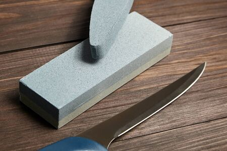 Grindstones. Two whetstones and steel knife blade. Oval and rectangular double layer sharpening stone on wooden table background