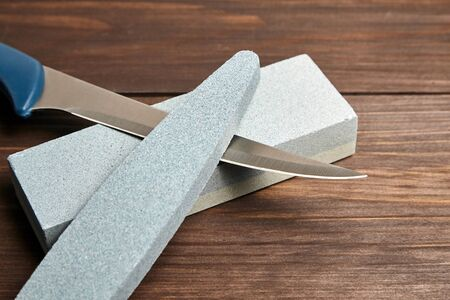 Whetstones and steel knife blade. Grindstones. Oval and rectangular double layer sharpening stone on wooden table background Reklamní fotografie