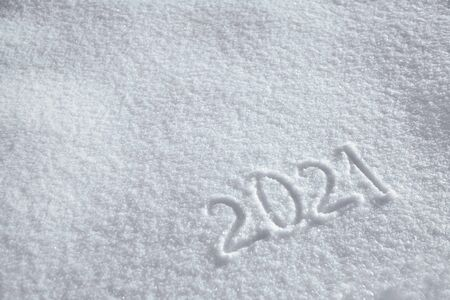 Numbers, calendar date, inscription 2021 on natural snowy surface in wintertime. Text, Winter New Year holiday background with copy space Imagens