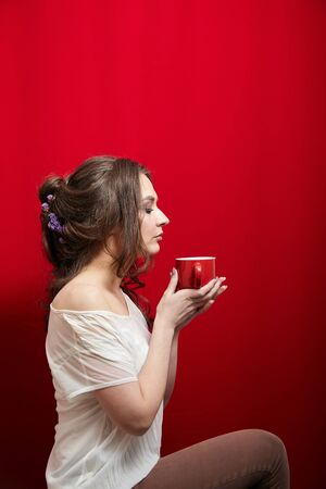 Lady inhales the aroma of coffee or tea. Young woman with a cup of beverage in her hands on red background