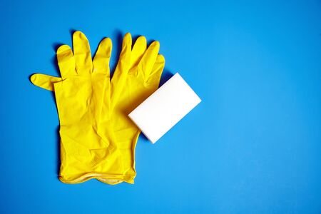 Yellow household gloves and white melamine sponge on blue background. Universal tool for cleaning various surfaces from dirt and stains