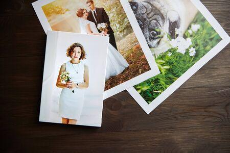 Impresiones fotográficas en lienzo. Muestra de fotografía estirada de mujer con envoltura de galería. Fotos impresas de un perro y una pareja de novios acostados sobre una mesa de madera. Vista superior Foto de archivo
