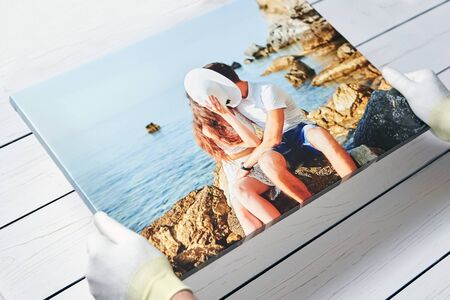 Photography printed on canvas with gallery wrap method of canvas stretching. Photo of kissing couple in love is in male hands