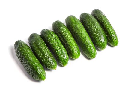 Row of fresh green gherkins isolated on white background