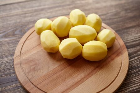 Peeled potatoes on wooden cutting board on brown table. Cooking food from natural products. Root vegetable. Raw ingredient: uncooked whole potatoes Stock Photo