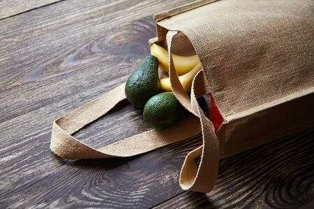 Reusable shopping bag with fresh fruits. Natural eco friendly material. Yellow bananas, green avocado, hessian or jute sack on brown wooden table. Useful organic products Stock Photo