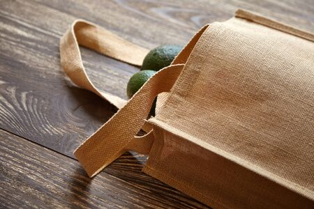 Reusable shopping bag with fresh fruits. Natural eco friendly material. Green avocados, hessian or jute sack on brown wooden table. Useful organic products