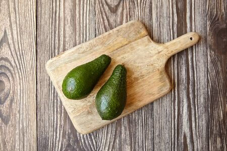 Avocados on a natural pine cutting board on wooden background. Two whole green fresh tropical fruits on brown table, top view Stock Photo