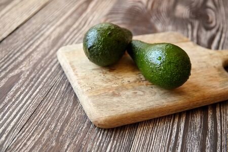 Avocados on a natural pine cutting board on wooden background. Two whole green fresh tropical fruits on brown table