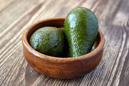 Avocados in a bowl on wooden background. Whole green fresh tropical fruits on brown table