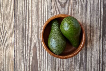 Avocados in a bowl on wooden background. Whole green fresh tropical fruits on brown table, top view