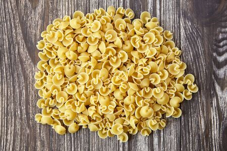 Funghetti pasta. Uncooked italian pasta on brown wooden table, top view Stock Photo