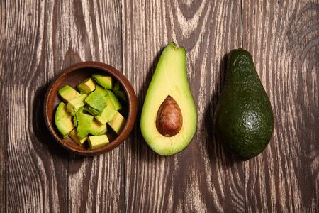 Chopped avocados in a bowl on wooden background. Half avocado with pulp and seed, whole green fresh tropical fruit on brown table, top view