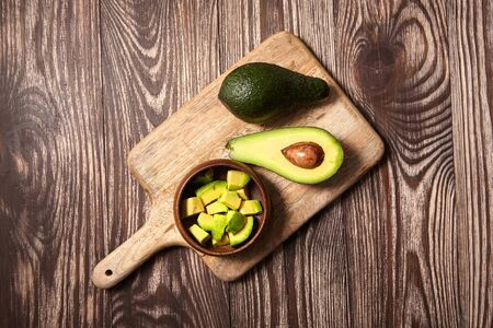 Chopped avocados in a bowl on cutting board on wooden background. Half avocado with pulp and seed, whole green fresh tropical fruit on brown table, top view
