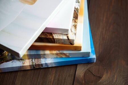 Leinwanddrucke fotografieren. Gestapelte bunte Fotos mit Galerieverpackungsmethode der Leinwandspannen auf Keilrahmen, seitliche Seite