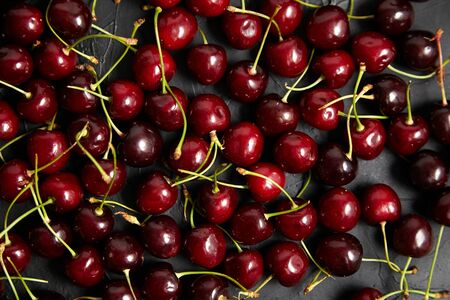 Cherries background. Red ripe berries scattered on a black table