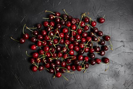 Cherries scattered on a black table. Red ripe berries on dark background, top view
