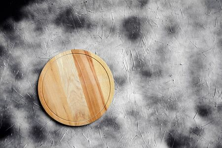 Empty round cutting board from beech wood on stone table with copy space, grey background, top view