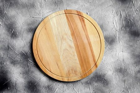Empty round cutting board from beech wood on stone table, grey background, top view Stock Photo