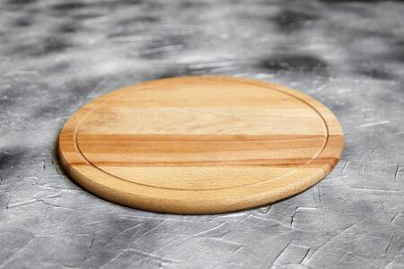 Leeres rundes Schneidebrett aus Buchenholz auf Steintisch, grauer Hintergrund, Seitenansicht Standard-Bild