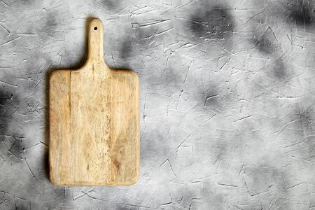 Empty cutting board from pine wood on  stone table, grey background, top view