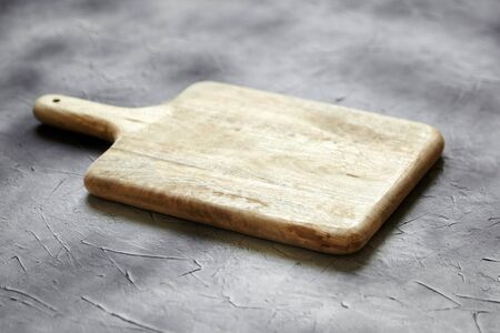 Empty cutting board from pine wood on  stone table, grey background, side view