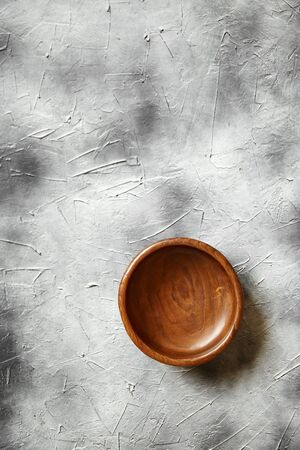 One empty wooden bowl on grey background. Single round salad bowl on stone table with black paint stains, top view