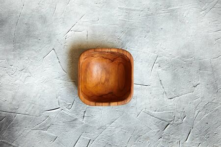 One empty wooden bowl on grey background. Single square salad bowl on stone table with black paint stains, top view