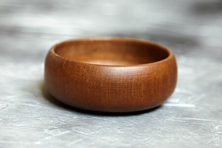 One empty wooden bowl on grey background. Single round salad bowl on stone table with black paint stains, side view