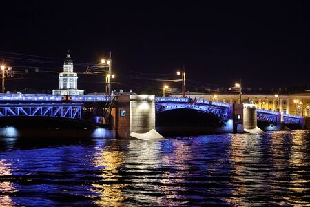 Palace Bridge across the Neva River. Cityscape with Kunstkamera building. Night city lights, ripples, colorful reflection in water. Saint Petersburg, Russia