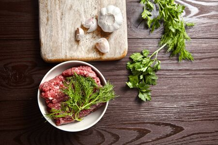 Bowl with raw minced meat, cutting board with fresh seasonings on a wooden background. White garlic heads and cloves, green dill and parsley leaves. Ground beef and condiments, top view