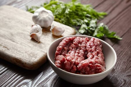 Bowl with raw minced meat, cutting board with fresh seasonings on a wooden background. White garlic heads and cloves, green dill and parsley leaves. Ground beef and condiments