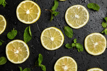 Lemon slices and green mint leaves on black background with water drops, top view. Fresh tropical fruit, yellow citrus, flat lay