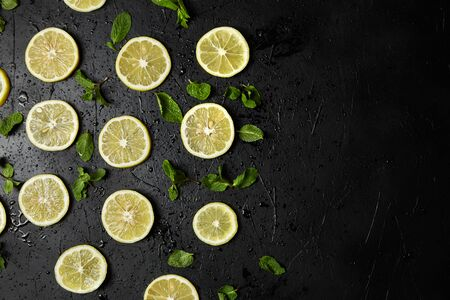 Lemon slices and green mint leaves on black background with water drops, top view. Fresh tropical fruit, yellow citrus, flat lay, copy space Stok Fotoğraf