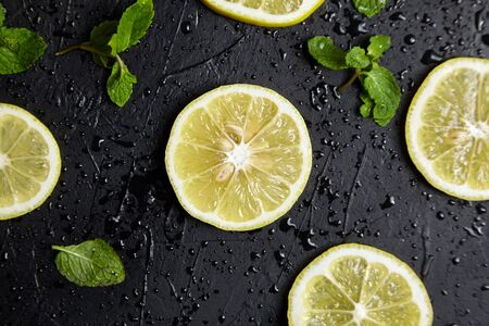 Lemon slices and green mint leaves on black background with water drops, closeup, top view. Fresh tropical fruit, yellow citrus, flat lay