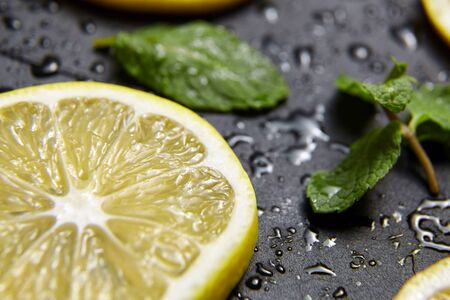 Lemon slice and green mint leaves on black background with water drops. Fresh tropical fruit, yellow citrus closeup