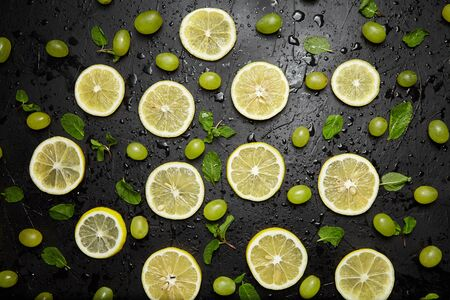 Lemon slices, green mint leaves and grapes on black background with water drops, top view. Fresh tropical fruit, yellow citrus and berry, flat lay