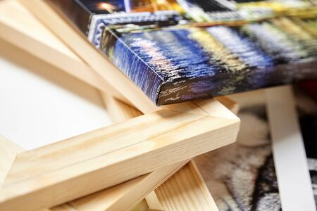 Print photography on canvas. Colorful photo, stack of wooden stretcher bars. Stretched photo canvas with gallery wrapping method, closeup, side view Stockfoto