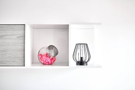 Shelf hanging on a white wall. A lamp and a glass jar with pink candies standing on a shelf. Decorative elements in interior of a living room, bright apartment