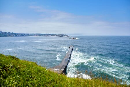 Landscape with dike and ocean waves, Digue de Sainte-Barbe in Saint Jean de Luz, France. The waters of the Bay of Biscay. Atlantic seascape. Engineering structure for protection against sea waves