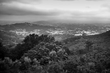 Hilly rural landscape in the foothills at cloudy summer day. Atlantic Pyrenees, France. Overcast weather. Black and white