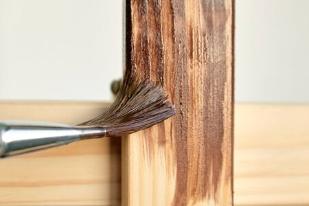 Protective acrylic varnish coating of wooden surface. Wood Finishing. Paintwork. A synthetic paint brush, easel, brown color varnish