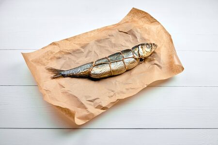 Hot smoked fish, kippered herring. Twine tied fish in craft paper on wooden table. Smoked herring on packaging paper on wooden background