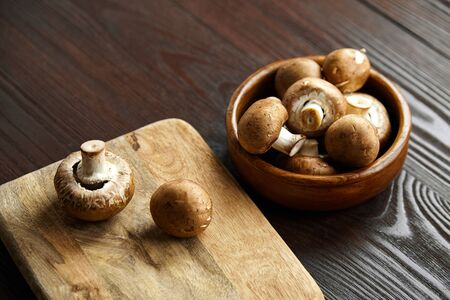 Mushrooms on cutting board, many fresh brown champignons in bowl on a wooden background. Uncooked food ingredient, selective focus