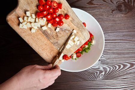 Person cooking vegetable salad. Red ?herry tomatoes with salad cheese on cutting board. Female hands with knife, food ingredients and a white ceramic bowl on wooden table, selective focus
