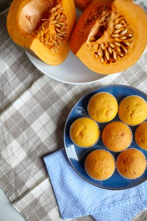 Pumpkin muffins and fresh pieces of pumpkin on blue plate on table with tablecloth, homemade bakery, selective focus. Vegetable, plant-based food, top view