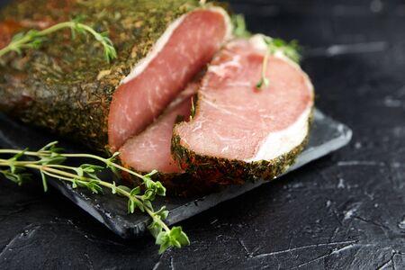Gerky pork with spices, fresh green thyme, slate cutting board on black stone table. Polendwitz is a jerky tenderloin. Sun-dried filet, selective focus